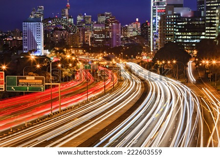 Australia NSW Sydney city Cahill expressway at sunset with long blurred traffic lights multi-lane motor road towards CBD, harbour bridge and illuminated landmarks - stock photo
