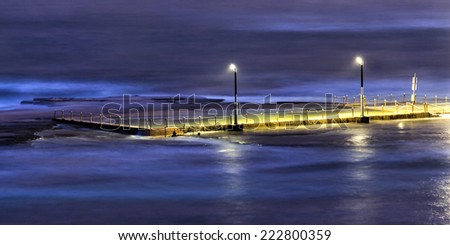 australia pacific ocean beaches public infrastructure mona vale rock pool distant elevated panoramic view after sunset with illuminated overflown swimming facility - stock photo