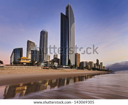Australia Queensland SUrfers Paradise at Gold Coast CBD skyscrapers on the Beach at sunrise with wavers surf and reflection on the sand