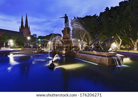 australia Sydney Archibald fountain in Hyde Park at sunset with lights illumination, blurred streams of water and St Mary's cathedral in background - stock photo