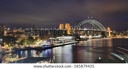 australia sydney bridge panoramic view at sunset from circular quay passenger ferries terminal illuminated lights and blurred tails of ships - stock photo