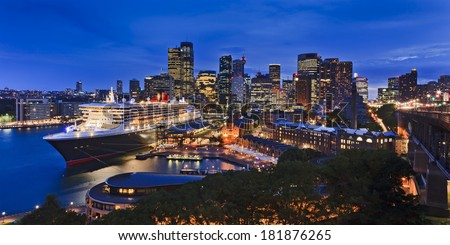 australia Sydney CBD panoramic view from harbour bridge to Circular quay passenger terminal with docked liner illuminated skyscrapers and the city - stock photo