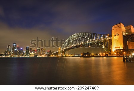 Australia SYdney City CBD and Harbour Bridge panoramic view across the harbour to landmarks illuminated at sunset - stock photo