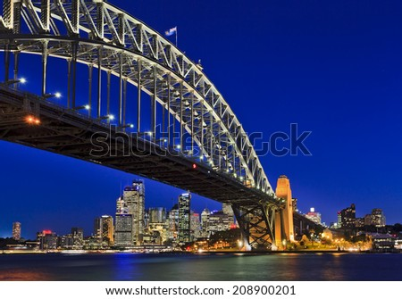 australia Sydney city cbd and harbour bridge view across the water at sunset brightly illuminated - stock photo
