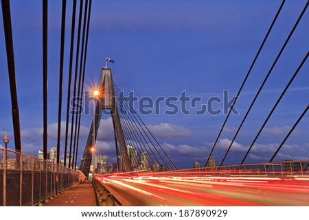 australia sydney city CBD ANZAC bridge cables and masts at sunset with driving cars in heavy traffic with illuminated blurred lights  - stock photo