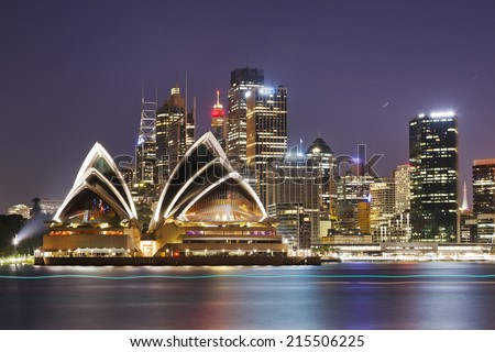 Australia SYdney City CBD close up view over harbour waters at sunset dark sky and reflections of city lights in blurred water - stock photo