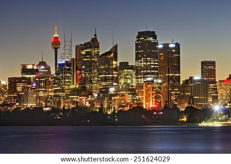 Australia SYdney city CBD skyscrapers and tower close up view over sydney harbour at sunset with full illumination