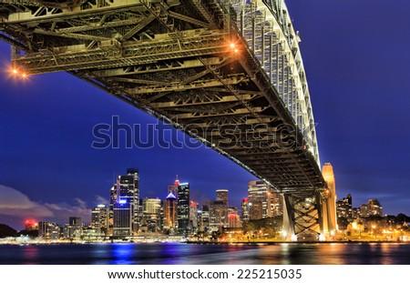 Australia Sydney city CBD view from under the Harbour Bridge at sunset illuminated cityscape landmark - stock photo