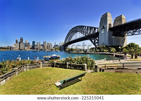 Australia Sydney city CBD view with harbour bridge and small green park among harbour with empty bench waiting for visitors to enjoy city view on summer sunny day - stock photo