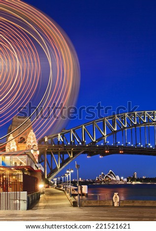 Australia Sydney City Harbour bridge and other landmarks at sunset illuminated with lights and blurred motion of entertainment - stock photo