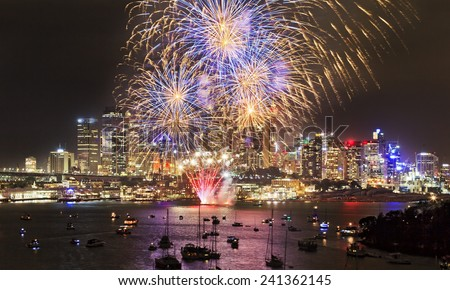 Australia Sydney city highlighted at New Year celebration fireworks with colourful fire balls above skyscrapers and harbour  - stock photo