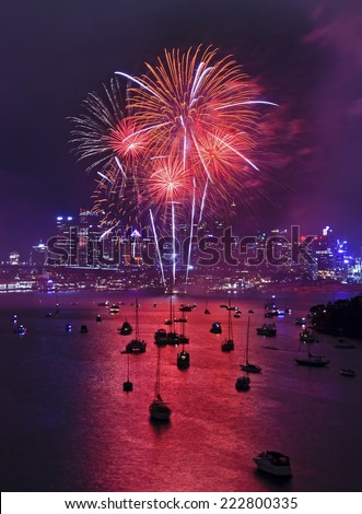 Australia Sydney New Year fireworks midnight vertical view on red balls over city CBD skyscrapers and reflection in harbour waters - stock photo