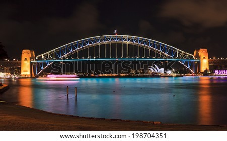 australia sydney NSW city landmarks harbour bridge and harbour waters at vivid light show illuminated with lights reflecting after sunset - stock photo