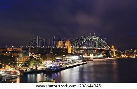 Australia Sydney view from circular quay at Harbour bridge at sunset illuminated city landmarks  - stock photo