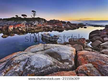 Australia Tasmania bay of fires binalong fishing boat anchored in still protected lagoon with a view on an ocean at sunrise - stock photo