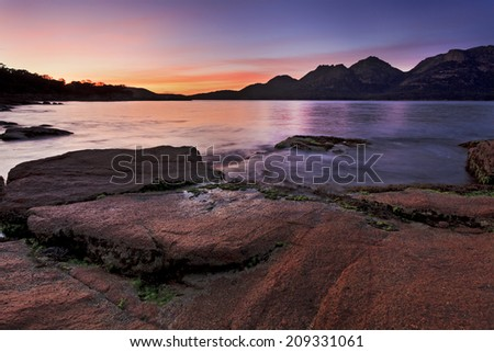 Australia Tasmania coles bay at Freycinet national park coastal oceanic sunrise rising sun over Hazards mountain range and red basalt rocks - stock photo