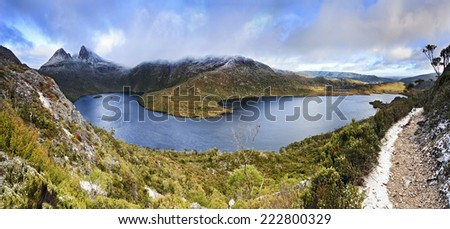 australia Tasmania Cradle Mountain national park panoramic view over Dove lake and surrounding mountain ranges with Cradle Mountain snow covered peaks sunrise in winter - stock photo