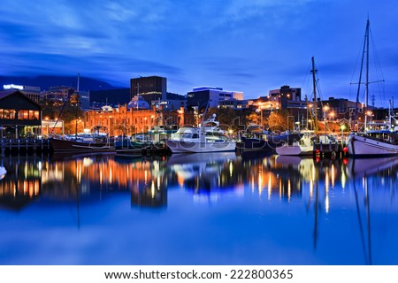 Australia Tasmania Hobart sullivan's cove at sunset illuminated buildings gallery and docked yachts with lights - stock photo