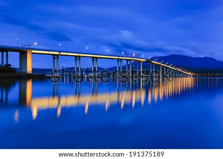 Australia Tasmania Hobart Tasman bridge over Derwent river at sunrise illuminated and reflection in still waters cityscape panorama