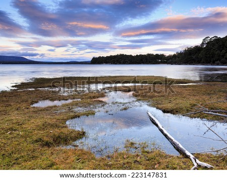 Australia Tasmania St CLair lake still water at sunset with red-blue blurred sky and reflective puddles in the foreground - stock photo