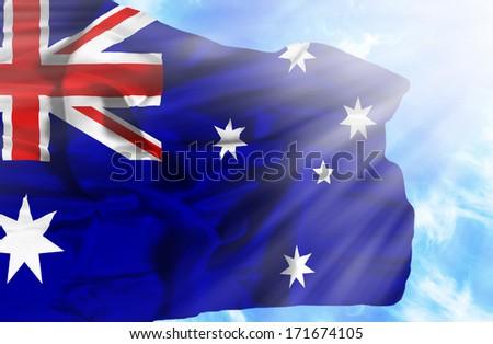 Australia waving flag against blue sky with sunrays - stock photo