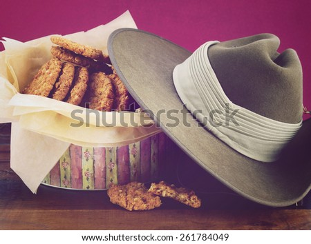 Australian Anzac biscuits in vintage biscuit tin with army soldier slouch hat, and applied retro vintage style filters.  - stock photo