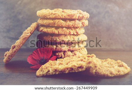 Australian Anzac biscuits on wood table with slate background and applied retro vintage filters and added light effects. - stock photo