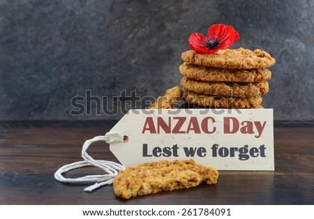 Australian Anzac biscuits with Anzac DAy, Lest We Forget message on dark wood and slate background. - stock photo