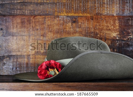 Australian army slouch hat on dark recycled wood with remembrance red poppy for Anzac Day or Remembrance Armistice Day. - stock photo