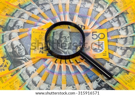 Australian banknote under a magnifying glass is being inspected - stock photo