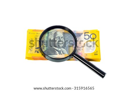 Australian banknote under a magnifying glass is being inspected on white background - stock photo