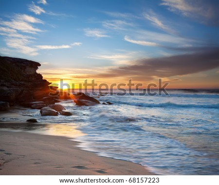 australian beach at sunrise with rushing wave in foreground - stock photo