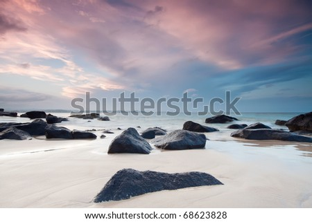 australian beach at twilight with interesting rocky foreground - stock photo