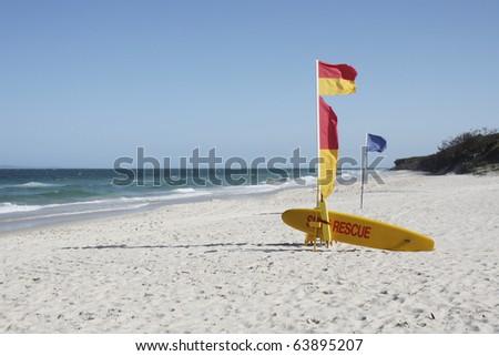Australian Beach Surf Rescue surfboard and flags on Bribie Island beach, Queensland, Australia - stock photo