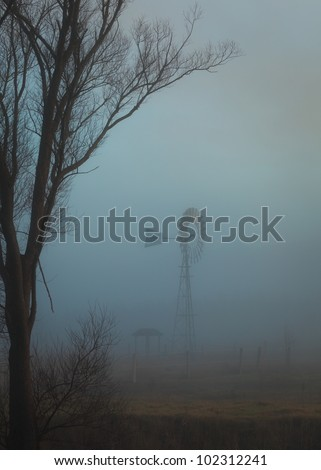 Australian bush landscape at dawn with fog and windmill.