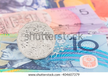 Australian 50 cent coin stand on dollar banknote money - stock photo