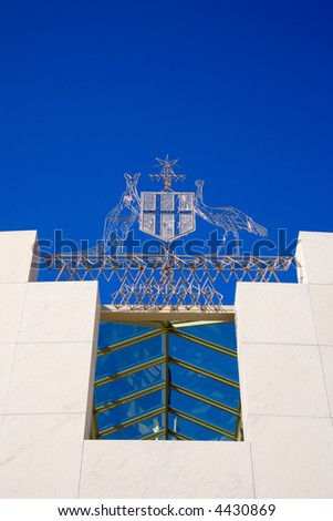 Australian Coat of Arms on Parliament House, Canberra, Australia. Emu and Kangaroo, Shield and Star, and with clear blue sky behind. Concept Australia. - stock photo