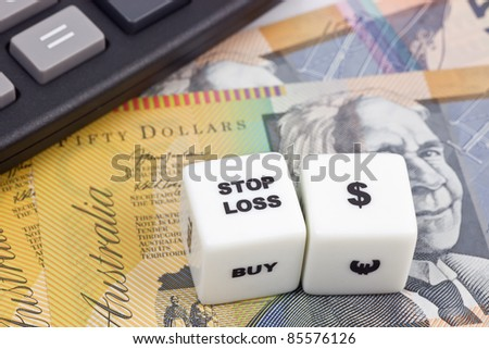 Australian currency with calculator and dice showing STOP LOSS - stock photo