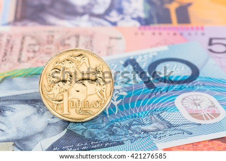 Australian dollar coin stand on banknote money - stock photo