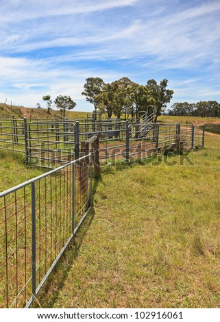 Australian farming scene with cattle fences and pens against a cloudy blue sky. - stock photo