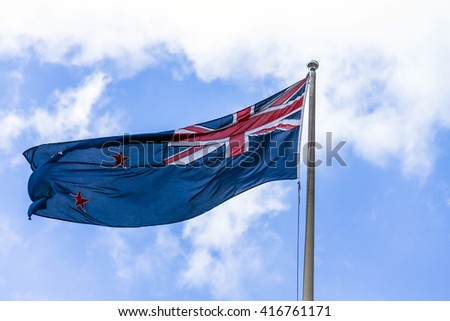 Australian flag waving against a blue sky with white clouds - stock photo