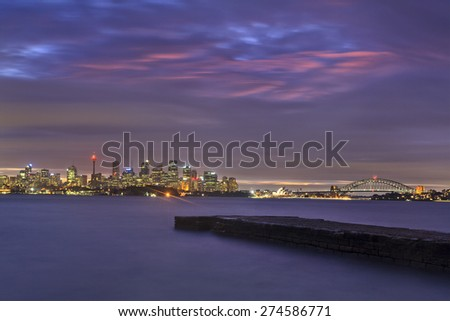 Australian major city Sydney cityscape after sunset during overcast cloudy weather. Illuminated CBD landmarks shot across Harbour with blurred water - stock photo