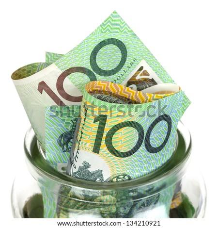 Australian money in jar, over white background.  One hundred dollar bills. - stock photo