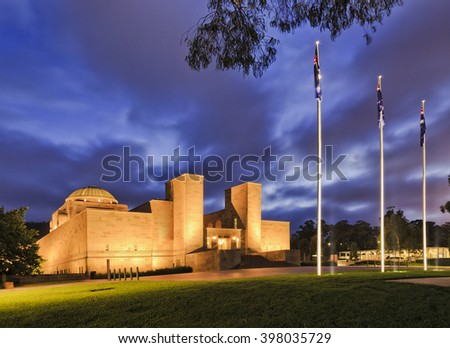 Australian national war memorial in Canberra at sunrise with bright illumination under blurred cloudy sky with nobody at dawn.