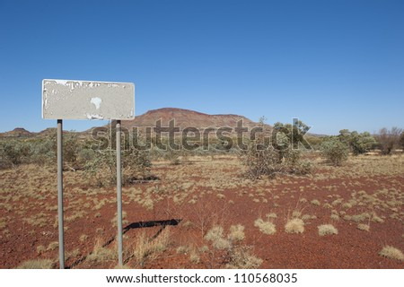 Australian outback landscape, with typical scenery of the Pilbara in Western Australia, red earth, spinifex grass and hills in the background, plus empty sign, blue sky as copy space. - stock photo