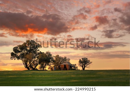 Australian outback sunset.  Old farm house, crumbling walls and verandah w sits abandoned on a hill at sunset. The last sun rays stretching across the landscape painting the grass in dappled light  - stock photo