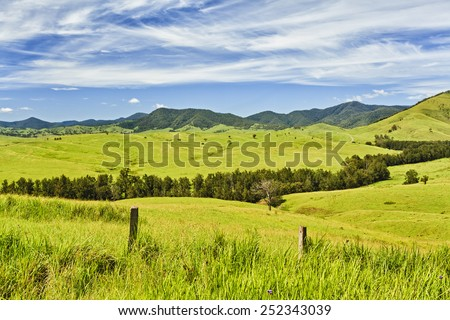 australian rural NSW remote agricultural farm with highly developed grazing land for steer production at cloudy thunderstorm weather view from side road over fence - stock photo