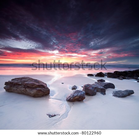 australian seascape at dawn with rocks in foreground (miami beach, queensland, australia) - stock photo