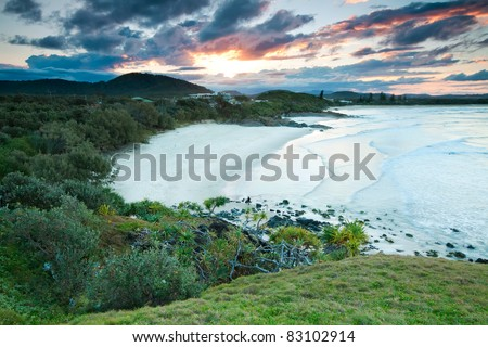australian seascape at sunset with native trees and beautiful beach in foreground (cabarita,nsw,australia) - stock photo