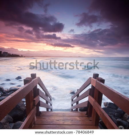 australian seascape during twilight with stairs leading towards the ocean in foreground (rainbow bay beach,tweed heads,nsw) - stock photo